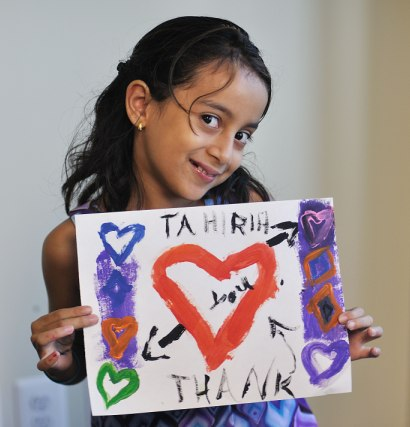 Tahirih client's child holds up a homemade thank you card